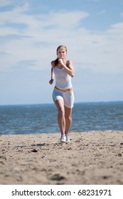 Beautiful young sport woman running on beach on sunny summer day