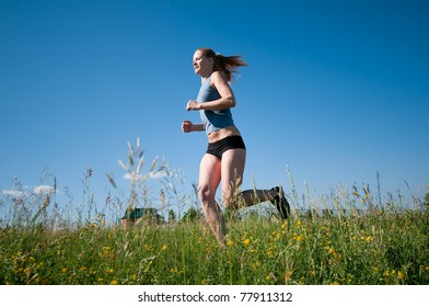 Beautiful young sport woman running over green grass on sunny summer day