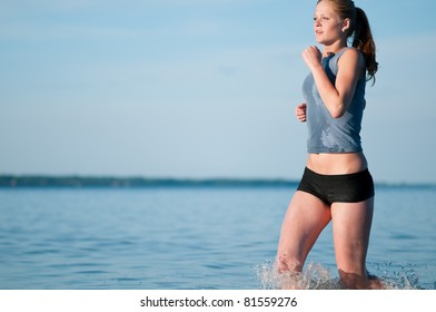 Beautiful young sport woman running in water on sunny summer day