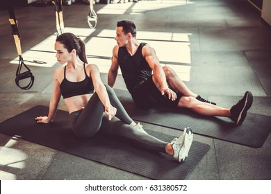 Beautiful young sports couple is stretching after workout in gym