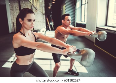 Beautiful young sports couple is working out with kettlebell in gym