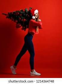 A beautiful young sports fashion woman dressed in sportswear and a Santa Claus hat, is holding a Christmas tree decorated with balls on her shoulder. To be in sports form in the new year.