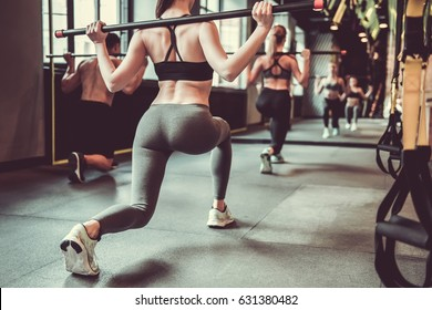 Beautiful young sports people are doing lunges with barbell while working out in gym