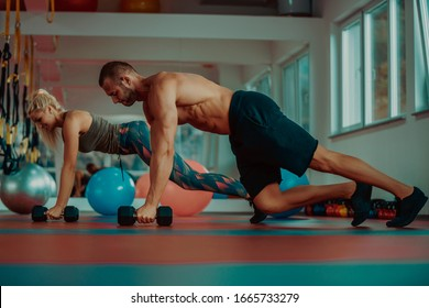 Beautiful young sports people are working out with dumbbells in gym