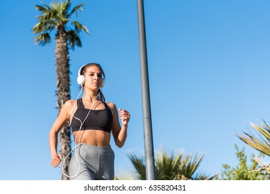beautiful young sports Woman running jogging in a park outdoors listening music
