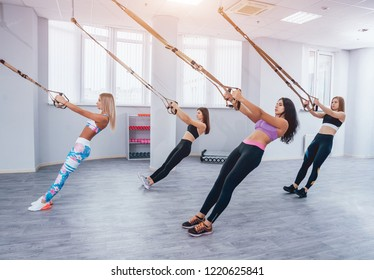 Beautiful young sports women are working out with TRX in gym. Light background