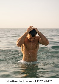beautiful young  sportsman is swimming in the sea, sexy male is wetting his hair.