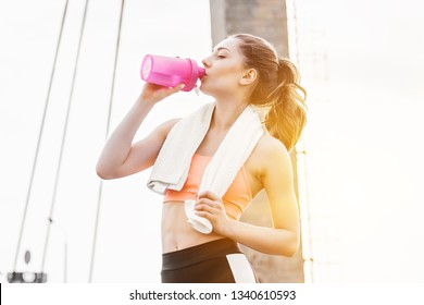 Beautiful young sportswoman drinking water from shaker while standing on bridge. Slender fitness girl in stylish sportswear posing outdoors. Doing workout in city. Sports girl with bottle of water