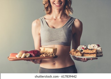 Beautiful young sportswoman is holding a wooden tray with healthy food and a plate with cakes, on gray background