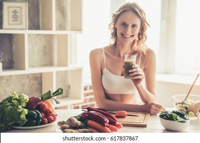 Beautiful young sportswoman is looking at camera and smiling while cooking healthy food in kitchen at home