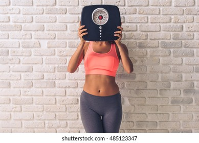 Beautiful young sportswoman in sportswear hiding behind the weigh scales, on white brick wall background