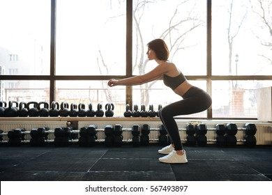 Beautiful young sportswoman standing and doing squats in gym