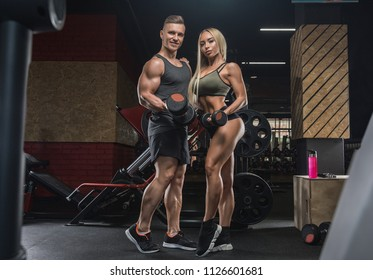 beautiful young sporty sexy couple showing muscle and workout in gym during photoshooting
