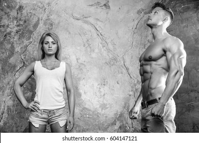 Beautiful young sporty sexy couple men and a woman posing showing muscle and workout in gym