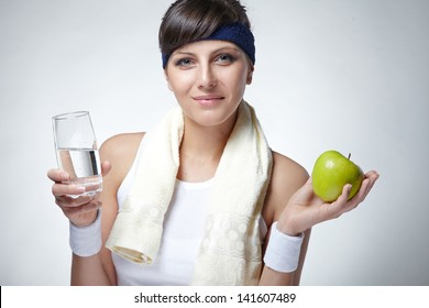 beautiful young sporty woman drinking mineral water and holding an apple