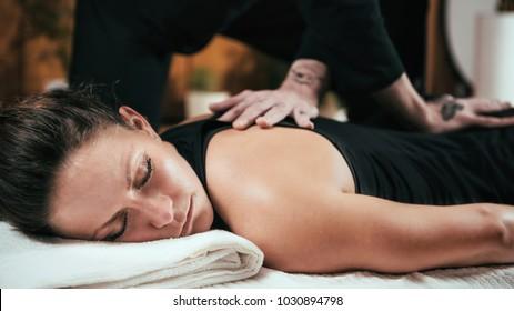Beautiful young sporty woman enjoying shiatsu back massage, lying on the wooden floor, wearing black top