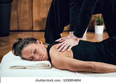 Beautiful young sporty woman enjoying shiatsu back massage, lying on the wooden floor, wearing black top