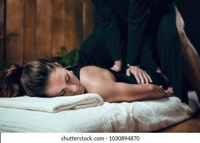 Beautiful young sporty woman enjoying shiatsu back massage, lying on the floor, wearing black top