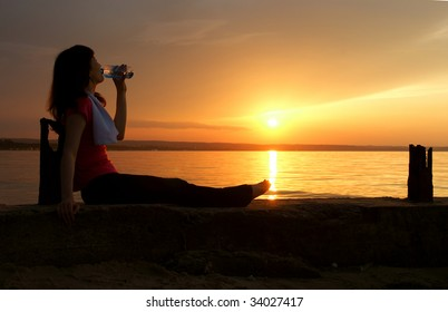 Beautiful young sporty woman to sit and drinking in front of a sunset.