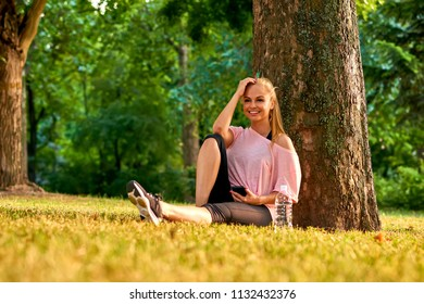 Beautiful young sporty woman sitting at a tree in a park in the sunset