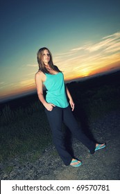 Beautiful young sporty woman standing on a road at summer sunset