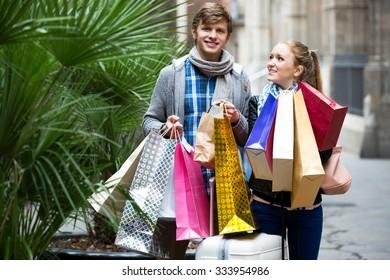 Beautiful young spouse walking through European town and carrying shopping bags