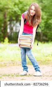 beautiful young student girl standing in park and holding pile of heavy books in her hands. Looking into the camera. Summer or spring green park in background