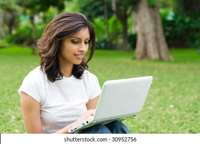 beautiful young student using laptop on grass