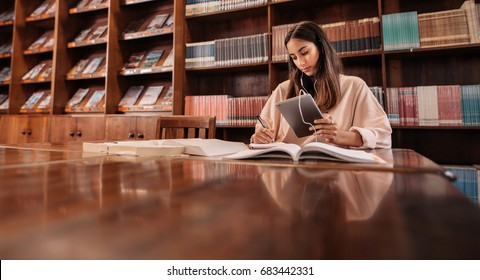 Beautiful young student using tablet pc while writing notes in the library. College student taking notes from reference book and listening music from digital tablet.