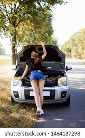 Beautiful young student woman checking engine of a broken car and tries to figure out how to repair her car