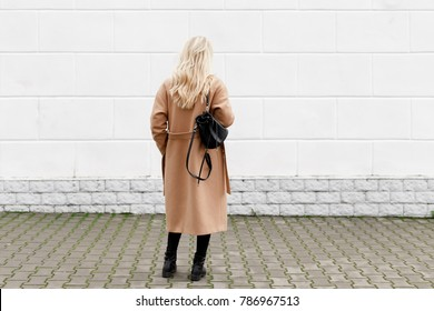 Beautiful young stylish blonde woman wearing long beige coat, black boots and backpack walking through the city streets. Trendy casual outfit. Street fashion. Back view.