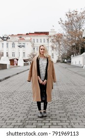 Beautiful young stylish blonde woman wearing long beige coat, jumper, flat shoes with snake print, black jeans and backpack walking through the city streets. Trendy casual outfit. Street fashion.