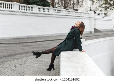 Beautiful young stylish brunette woman wearing midi green coat, black heeled boots, backpack, leopard print tights, purple scarf having fun on the city streets. Trendy casual outfit.