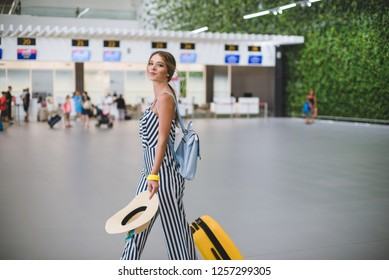 Beautiful young stylish Caucasian woman at the airport with a yellow suitcase and a straw hat goes on a journey.