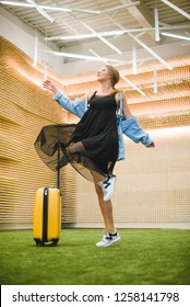 Beautiful young stylish Caucasian woman at the airport with a yellow suitcase goes on a journey.