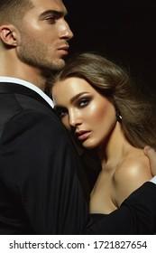Schönes junges stylisches Paar, Mann und Frau, in schwarzen Abendkleider in den Armen des jeweils anderen auf schwarzem Hintergrund posieren.
