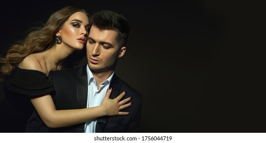 Beautiful young stylish couple, man and woman, in black evening dresses in each other's arms posing in the studio on a black background.
