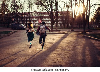 Beautiful young stylish couple running on city street at sunset. The guy with the backpack and the girl in the hat, skirt and sneakers. The concept of love, date, hurry