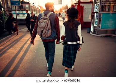 Beautiful young stylish couple while walking on a city street at sunset. The guy and girl are holding hands