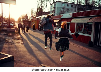 Beautiful young stylish couple while walking holding hands and running through the streets of the city at sunset. The guy with the backpack and the girl with the hat during a jump. The concept of love