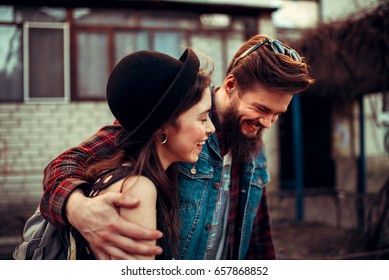 Beautiful young stylish couple while walking on a city street at sunset. Guy hugging a girl in a hat, laughing and talking. The concept of first love, a date, school years