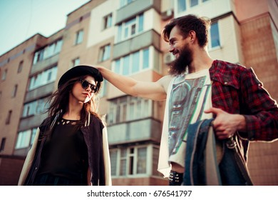 Beautiful young stylish couple while walking on a city street at sunset. Urban style. The concept of first love, a date, school years
