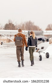 A beautiful, young, stylish couple in winter clothes on a snow-covered runway near a small pleasure plane.