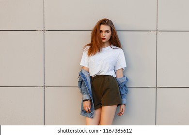 Beautiful young stylish woman in a jeans vintage jacket with a gray T-shirt and shorts stands near the wall