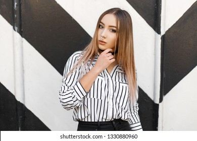 Beautiful young stylish woman in pierced nose in a stylish striped shirt in black jeans with a black choker around her neck poses near a black and white striped wall. Cute modern girl teenager.
