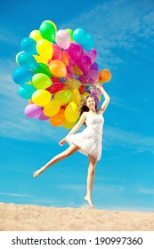 Beautiful young stylish woman with rainbow balloons in hands against the sky. Positive girl on nature. Smiling woman outdoors enjoying.