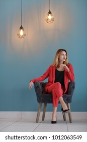 Beautiful young stylish woman sitting in armchair near color wall