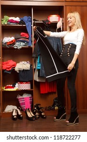 Beautiful young stylish woman stands near her wardrobe   and holding her dress