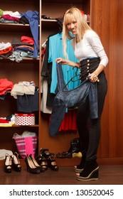 Beautiful young stylish woman stands near  wardrobe   and holding  dress