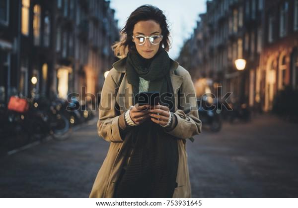 Linda jovem mulher elegante andando nas ruas da cidade da noite usando smartpone moderno, hipster feminina blogueiro digitando mensagem de texto em seu celular